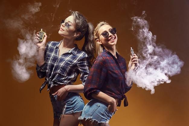 Stilvolle junge frau beim sonnenbrillerauchen Premium Fotos