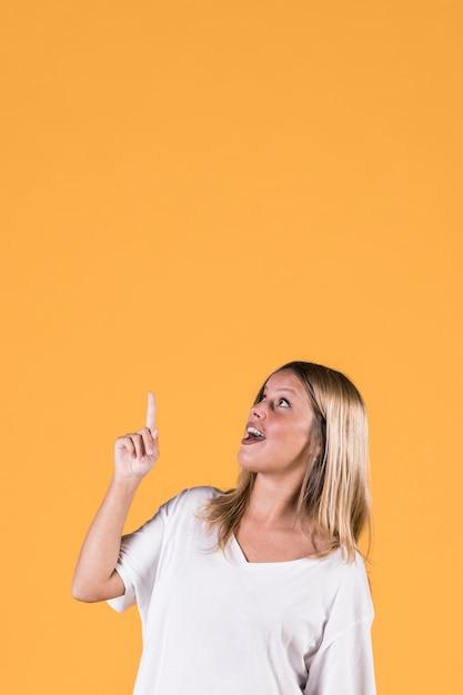 Stilvolle junge frau, die aufwärts richtung mit dem mund offen zeigt Kostenlose Fotos