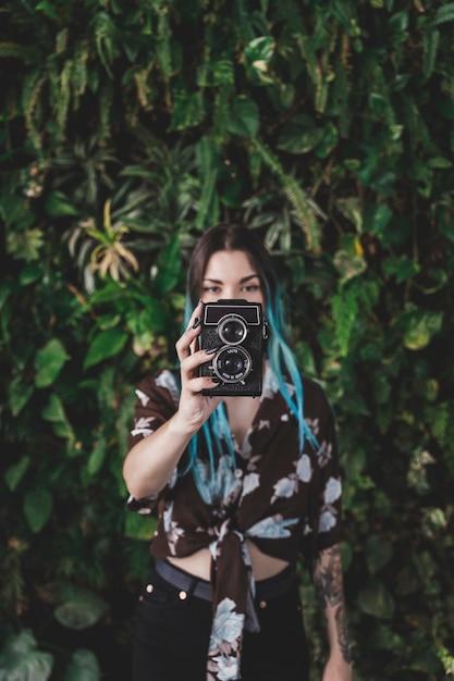 Stilvolle junge frau, die mit altmodischer kamera fotografiert Kostenlose Fotos