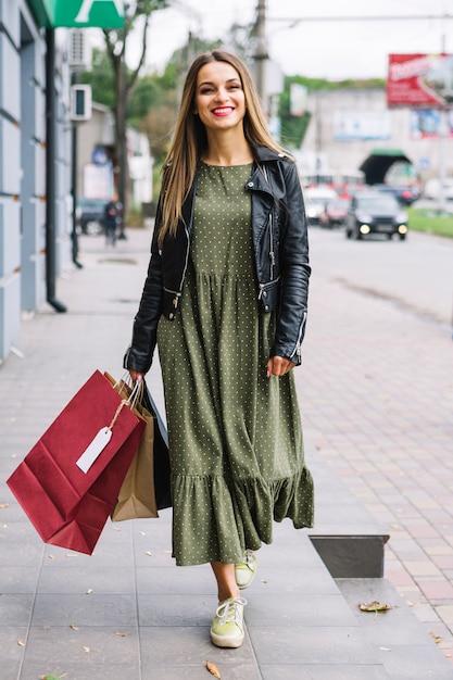 Stilvolle junge frau, die mit bunten einkaufstaschen auf straße geht Kostenlose Fotos