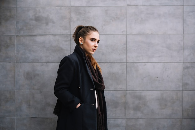 Stilvolle junge frau im mantel mit schal nahe grauer wand Kostenlose Fotos