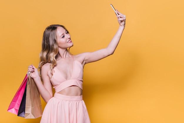 Stilvolle junge frau mit den taschen, die selfie nehmen Kostenlose Fotos