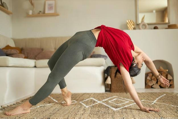 Stilvolle junge frau mit schönem flexiblem körper, der vinyasa flow yoga praktiziert, brückenhaltung oder urdhva dhanurasana tut Kostenlose Fotos