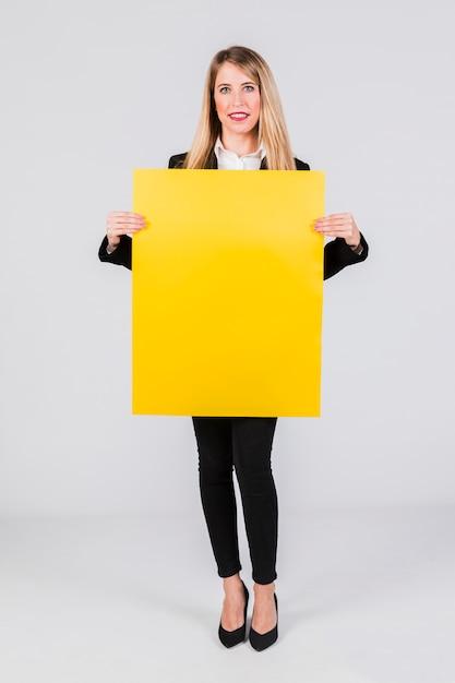Stilvolle junge geschäftsfrau, die das leere gelbe plakat steht gegen grauen hintergrund hält Kostenlose Fotos