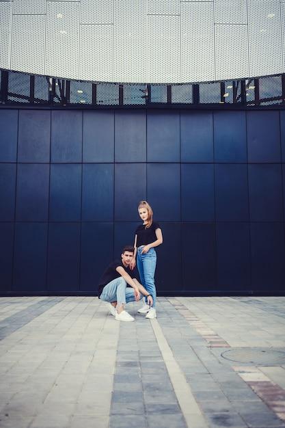 Stilvolle junge paare nahe blauer wand Premium Fotos