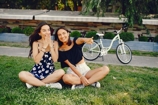 Stilvolle mädchen, die in einen sommerpark gehen Kostenlose Fotos