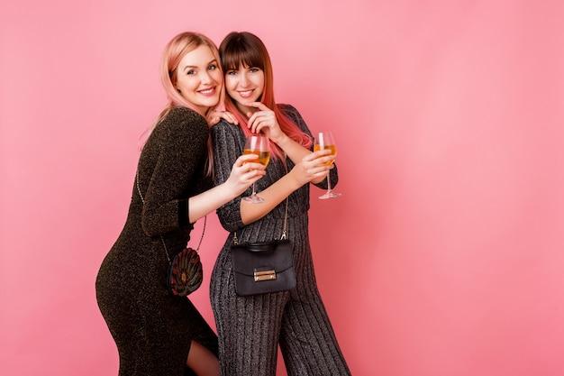 Stilvolle mädchen mit gläsern der alkoholgetränke, die auf hellrosa wand aufwerfen Kostenlose Fotos