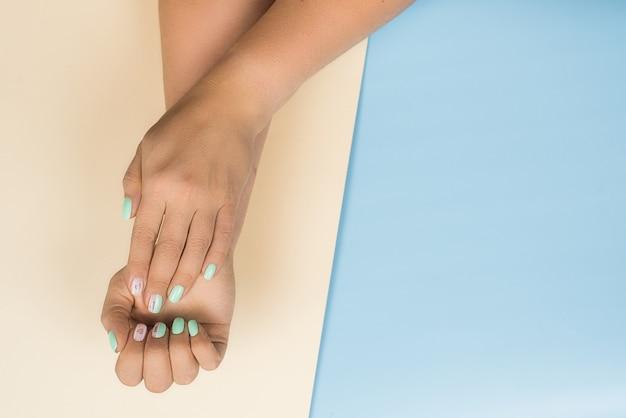 Stilvolle modische weibliche blaue neue maniküre mit herzen und die wörter lieben auf den nägeln. die hände der schönen frau auf beige und blau Premium Fotos