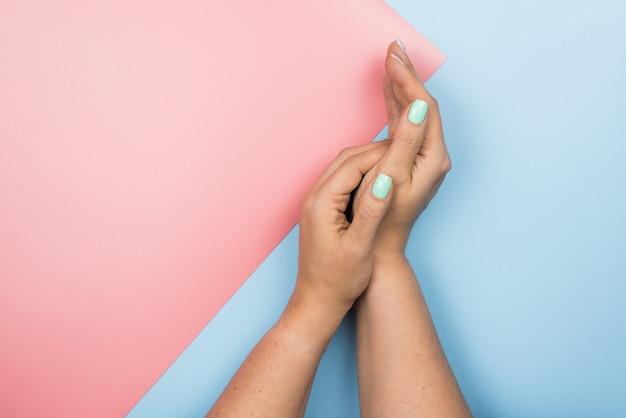 Stilvolle modische weibliche blaue neue maniküre. schöne hände der jungen frau auf rosa und blauem pastell Premium Fotos