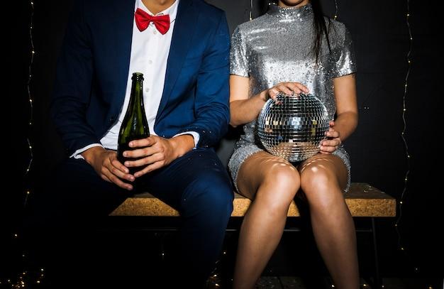 Stilvolle paare mit discokugel und flasche champagner Kostenlose Fotos