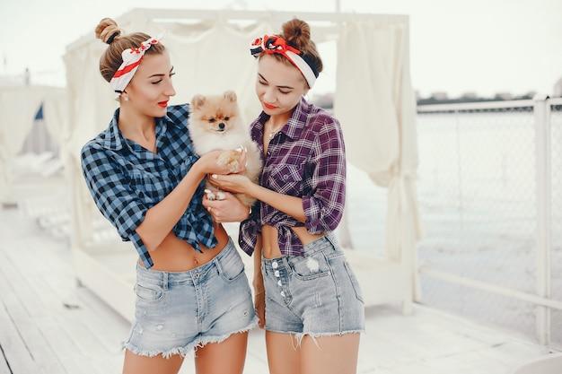 Stilvolle pin up girls mit dem kleinen hund Kostenlose Fotos
