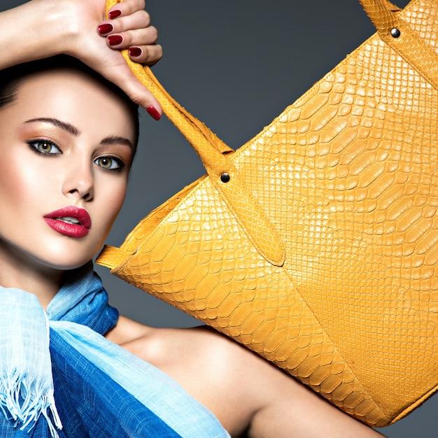 Stilvolle schöne frau, die blauen schal mit gelber handtasche trägt. Kostenlose Fotos