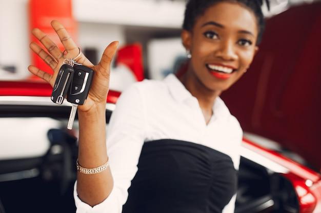 Stilvolle schwarze frau in einem autosalon Kostenlose Fotos