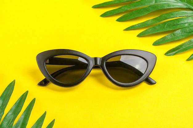 Stilvolle schwarze sonnenbrille und palmblätter auf trendigem gelb Premium Fotos