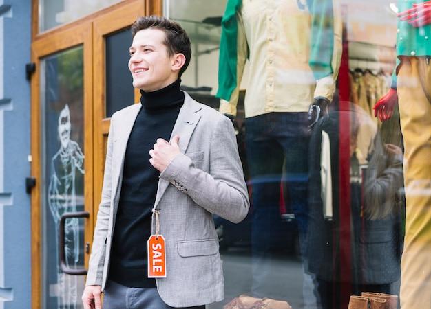 Stilvolle tragende jacke des jungen mannes mit verkaufstag stehend außerhalb des shops Kostenlose Fotos