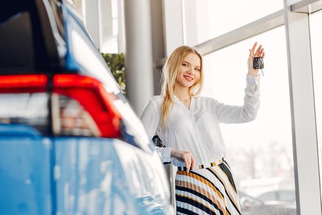 Stilvolle und elegante frau in einem autosalon Kostenlose Fotos