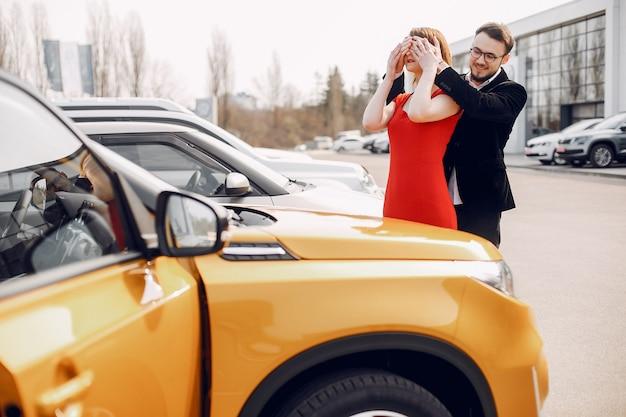Stilvolle und elegante paare im autosalon Kostenlose Fotos