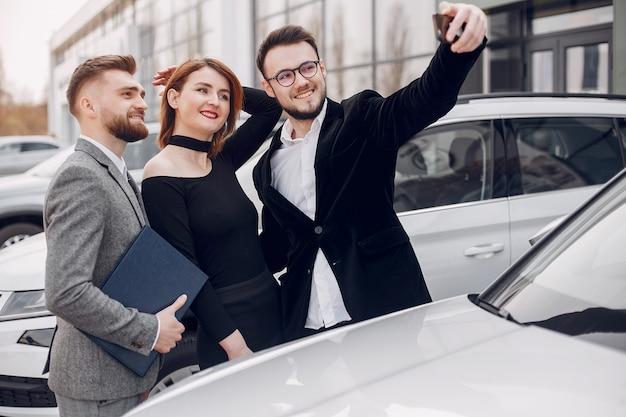 Stilvolle und elegante paare in einem autosalon Kostenlose Fotos