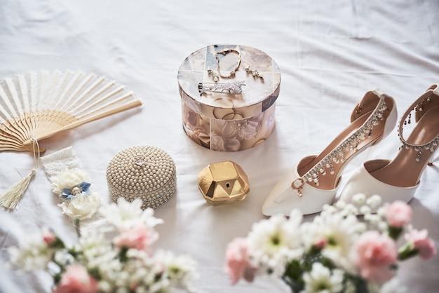 Stilvolle weiße hochzeit brautschuhe, parfüm, blumen und schmuck. Premium Fotos