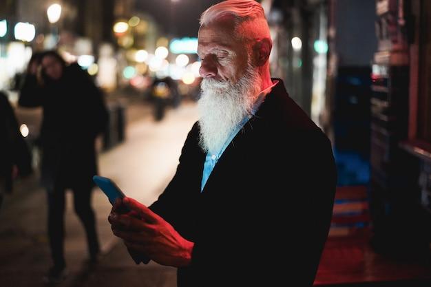 Stilvoller älterer mann, der smartphone verwendet, das in stadtstraße mit bokeh-lichtern im hintergrund steht - hipster-influencer, der spaß mit technologietrends hat - tech und freudiger älterer lebensstil - fokus auf gesicht Premium Fotos