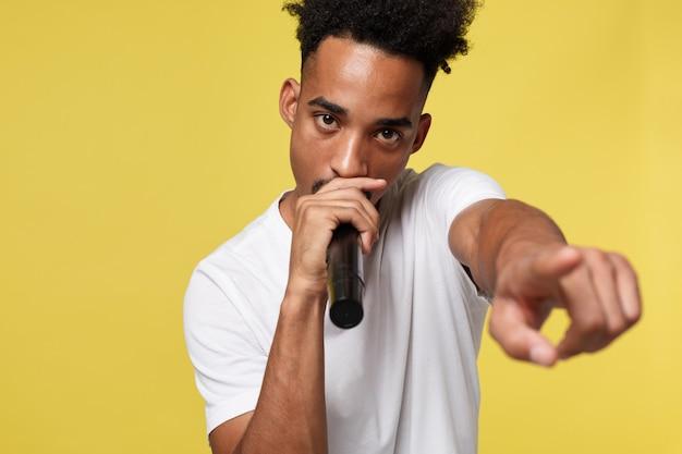 Stilvoller afroer-amerikanisch mann, der in das mikrofon lokalisiert auf einem gelbgoldhintergrund singt Premium Fotos