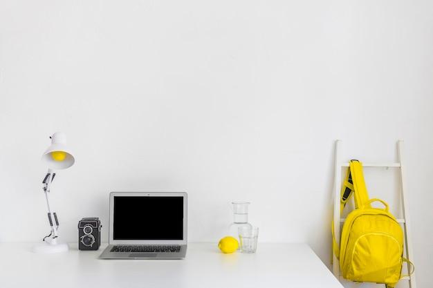 Stilvoller arbeitsplatz in den weißen und gelben farben mit rucksack und laptop Kostenlose Fotos