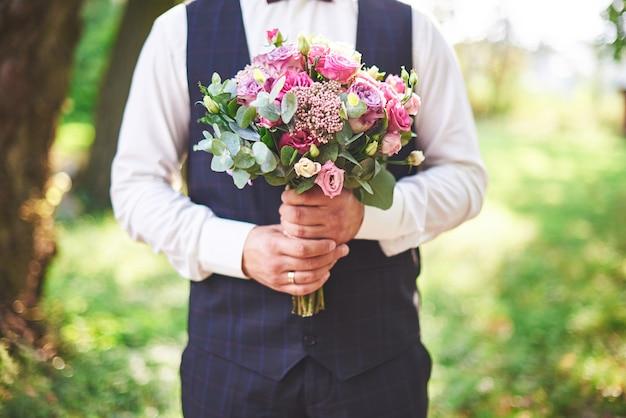 Stilvoller bräutigam, der einen zarten rosa hochzeitsstrauß hält. Kostenlose Fotos