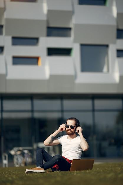 Stilvoller geschäftsmann, der im gras arbeitet Kostenlose Fotos