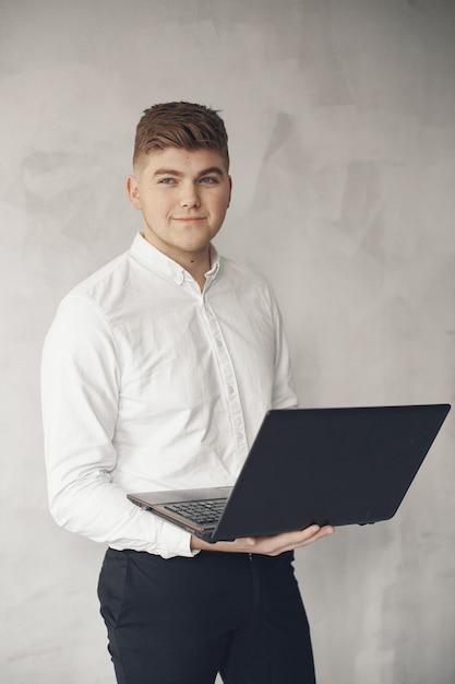 Stilvoller geschäftsmann, der in einem büro arbeitet und den laptop benutzt Kostenlose Fotos
