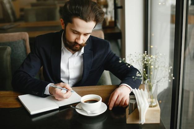 Stilvoller geschäftsmann, der in einem büro arbeitet Kostenlose Fotos
