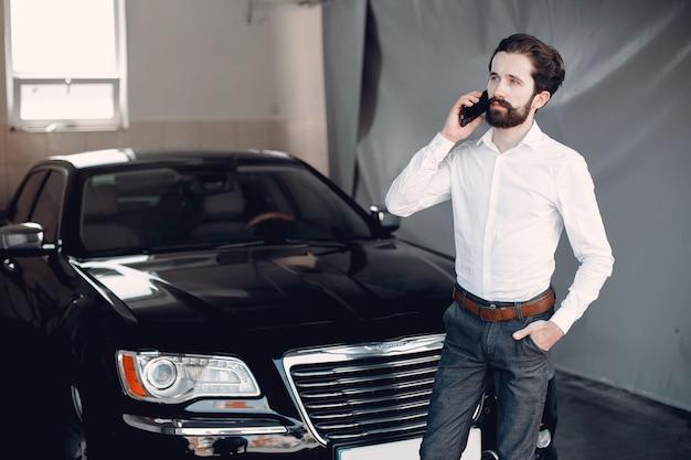 Stilvoller geschäftsmann, der nahe dem auto arbeitet Kostenlose Fotos