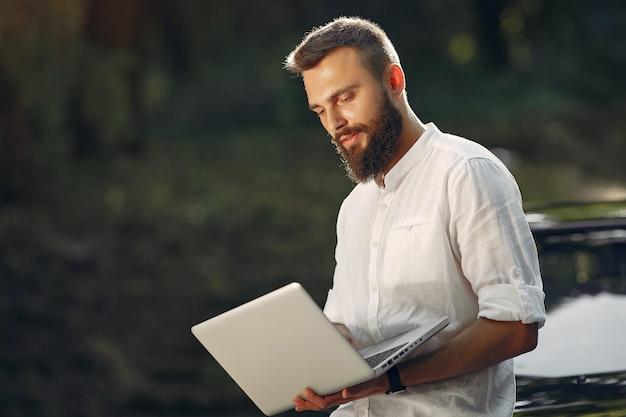Stilvoller geschäftsmann, der nahe dem auto steht und den laptop benutzt Kostenlose Fotos