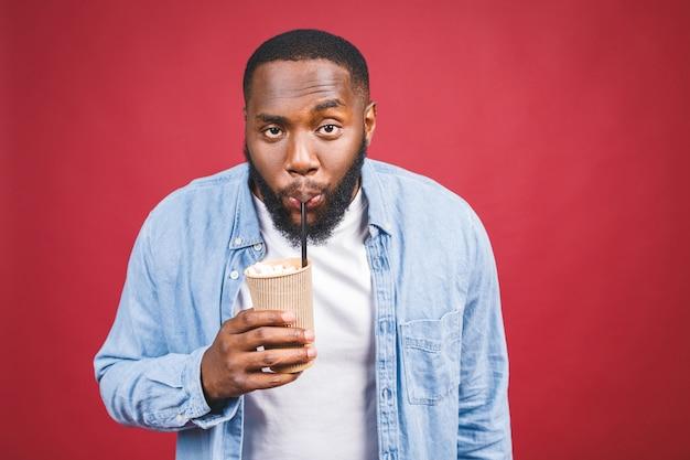 Stilvoller junger afroamerikanermann, der tasse des weggenommenen kaffees lokalisiert über rotem hintergrund hält. Premium Fotos