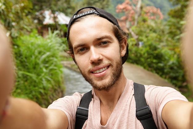 Stilvoller junger bärtiger männlicher blogger mit rucksack, der im freien aufwirft, während video aufzeichnet oder selfie nimmt Kostenlose Fotos