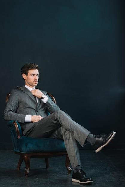 Stilvoller junger geschäftsmann, der auf lehnsessel gegen dunklen hintergrund sitzt Kostenlose Fotos