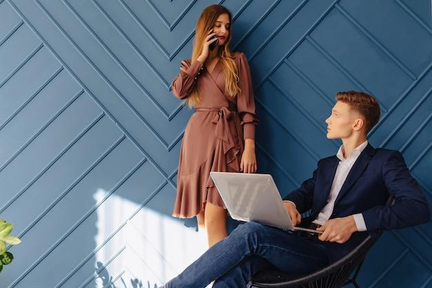 Stilvoller junger kerl mit laptop und mädchen mit telefon zusammen, junger geschäftsmann Premium Fotos