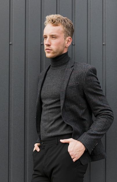 Stilvoller junger mann auf einem grauen hintergrund Kostenlose Fotos