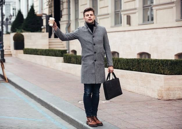 Stilvoller junger mann, der mitnehmerkaffee in der papierschale und anziehendes fahrerhaus auf leerer straße hält Kostenlose Fotos