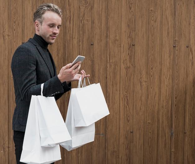 Stilvoller junger mann, der smartphone betrachtet Kostenlose Fotos