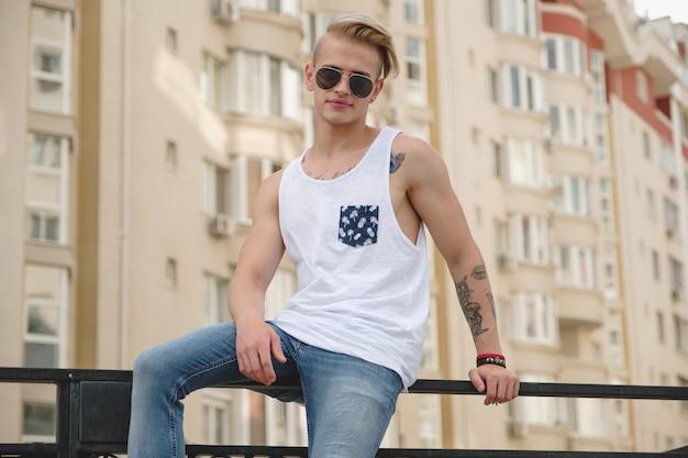 Stilvoller junger mann mit tätowierungen und modischer frisur Kostenlose Fotos
