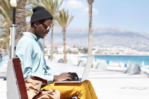 Stilvoller junger schriftsteller in hut und schatten, die auf keyborad auf laptop tippen Kostenlose Fotos