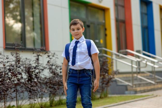 Stilvoller junger schüler in einem weißen hemd und in jeans mit einem rucksack Premium Fotos