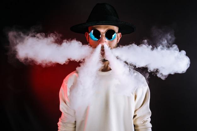 Stilvoller mann, der dampf luftstößt Premium Fotos