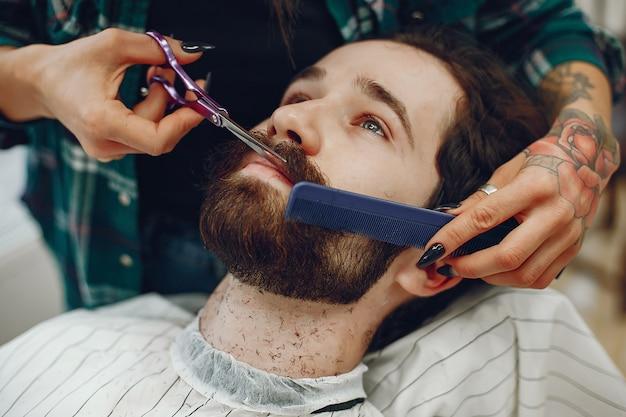 Stilvoller mann, der in einem friseursalon sitzt Kostenlose Fotos