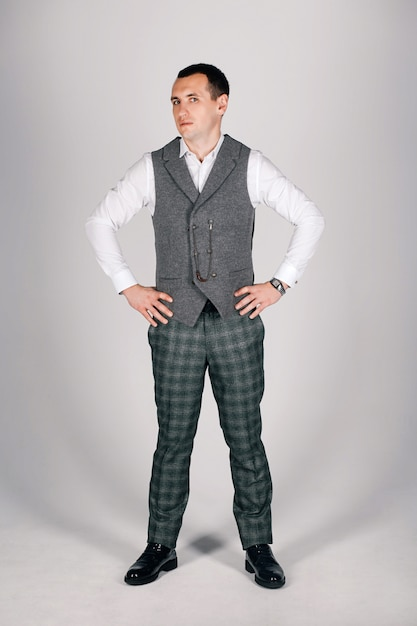 Stilvoller mann im karierten anzug auf einem grauen hintergrund Premium Fotos