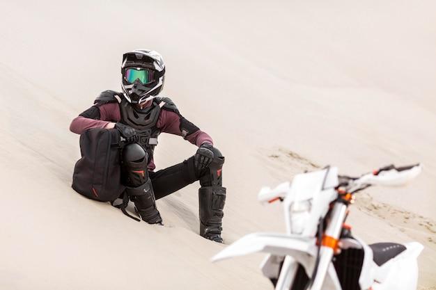 Stilvoller motorradfahrer, der sich in der wüste entspannt Kostenlose Fotos