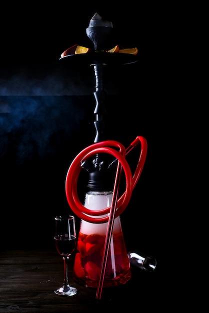 Stilvoller orientalischer shisha mit früchten auf einem schwarzen hintergrund. shisha-konzept Premium Fotos