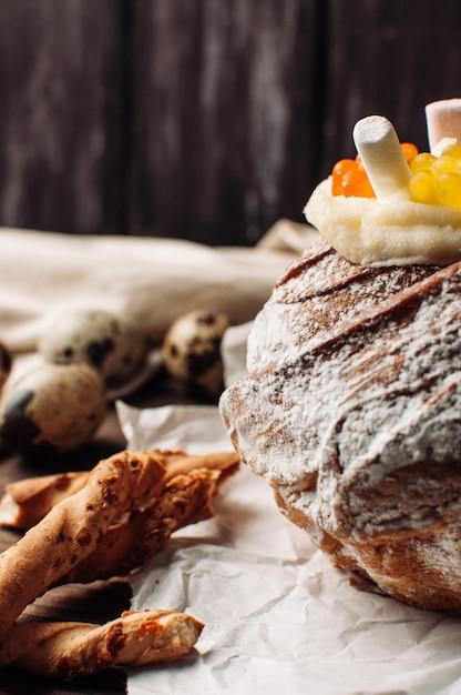 Stilvoller ostern-kuchen mit eibischen und gelee betrifft pergamentpapier auf einem rustikalen hölzernen hintergrund. Premium Fotos