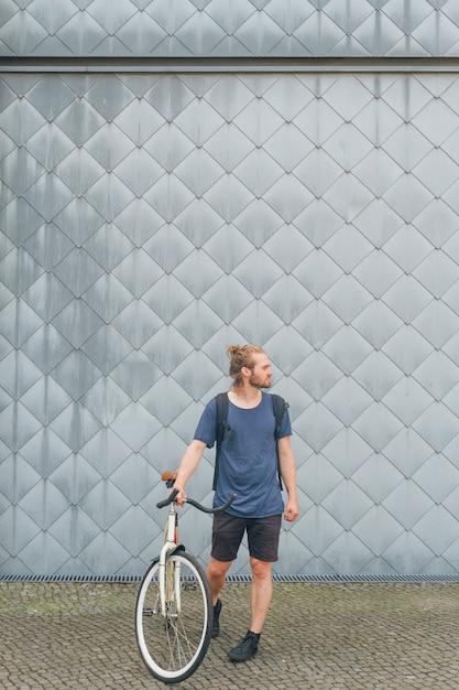 Stilvoller tragender rucksack des jungen mannes, der mit seinem fahrrad steht Kostenlose Fotos