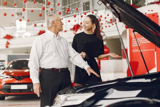 Stilvoller und eleganter alter mann in einem autosalon Kostenlose Fotos